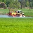 Stock Photo: Tractor spraying green field
