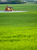 Tractor spraying on green farm — Stockfoto