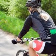 Woman riding a bike, motion blur — Stock Photo