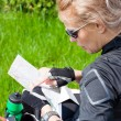 Woman on bicycle trip checking a map — Stock Photo