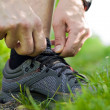 Stock Photo: Trail runner tying shoe