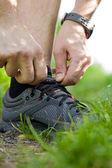 Trail runner tying shoe — Stock Photo