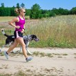 Woman running with dog — Stockfoto