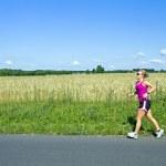 Running woman in summer nature — Stock Photo