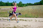 Woman running with dog — Stock Photo