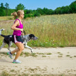 Woman running and walking a dog — Stock Photo