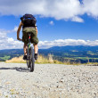 Riding a bike in mountains - Stock Photo