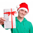 Man with santa hat holding christmas present — Stock Photo