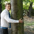 Stock Photo: A man hugging a tree