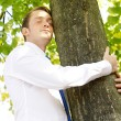 Stock Photo: Businessmhugging tree