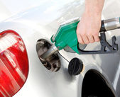 A man pumping gas in to the tank — Stock Photo