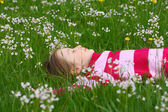 Child girl lying on a grass — Stock Photo