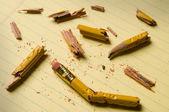 Fragmentos rotos lápiz sobre papel amarillo — Foto de Stock
