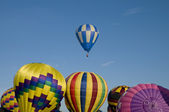 Hot-air balloon ascending over other inflating ones — Stock Photo