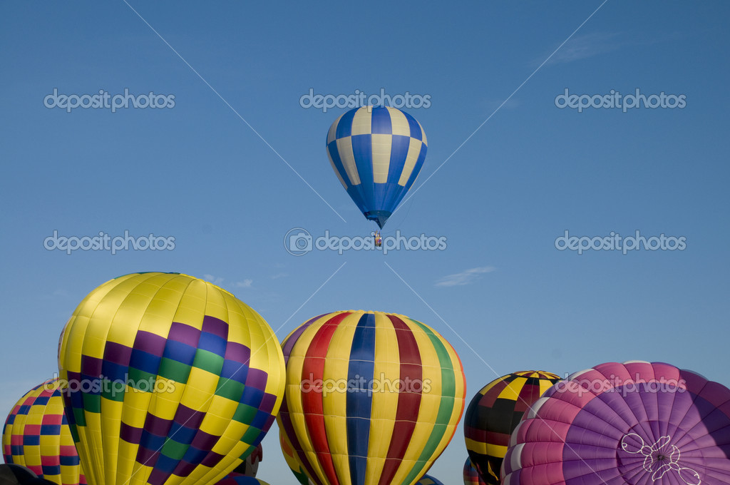 Hot-air balloon ascending over other inflating ones on the ground — Stock Photo #6432218