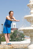 Happy young girl at a fountain. — Stock Photo