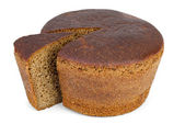 Round loaf of rye bread with piece cut — Stock Photo