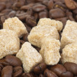 Few pieces of brown sugar over the coffee beans - Stock Photo