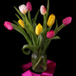 Beautiful pink and yellow tulips in vase isolated on black background — Stock Photo