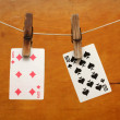 Playing cards (suits) hanging on a pin on a wooden background - Stock Photo