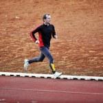 Adult man running on athletics track — Stock Photo