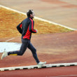 Adult man running on athletics track — Stock Photo #5647033