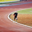 Stock Photo: Adult mrunning on athletics track