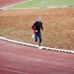 Постер, плакат: Adult man running on athletics track