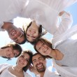 Group of happy young in circle at beach — Stock Photo