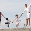 Happy young family have fun on beach at sunset — Stock Photo