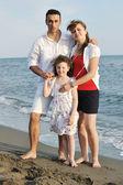 Família feliz jovem se divertir na praia — Fotografia Stock