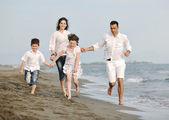 Счастливая молодая семья весело провести время на пляже — Стоковое фото