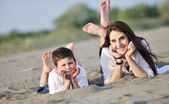 Anne ve oğul plaj rahatlatıcı — Stok fotoğraf