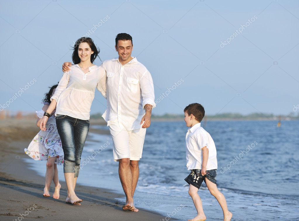 Happy young family have fun on beach run and jump  at sunset  Stock Photo #5765970