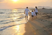 Happy young family have fun on beach at sunset — Stok fotoğraf