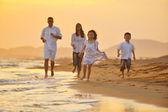 Mutlu bir aile var eğlenceli kumsalda gün batımında — Stok fotoğraf