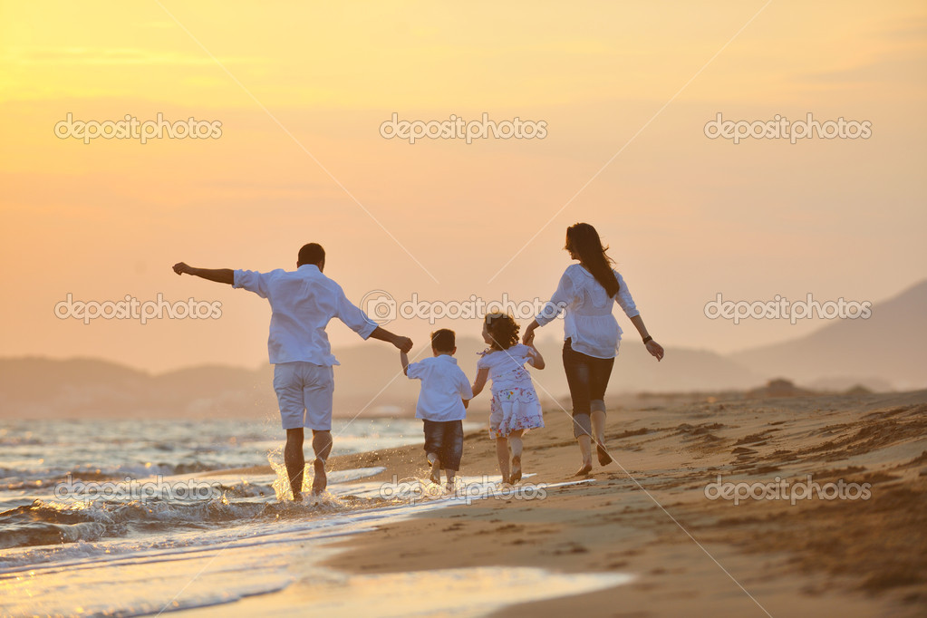 happy young family have fun on beach at sunset stock photo
