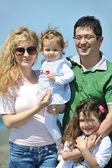 Glad ung familj ha kul på stranden — Stockfoto