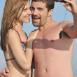 Happy young couple in love taking photos on beach — Stock Photo
