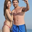 Happy young couple in love taking photos on beach — Stock Photo #5826291