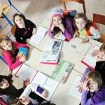 Happy kids with teacher in school classroom — Stock Photo #5826675