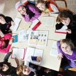 Happy kids with teacher in school classroom — Stock Photo