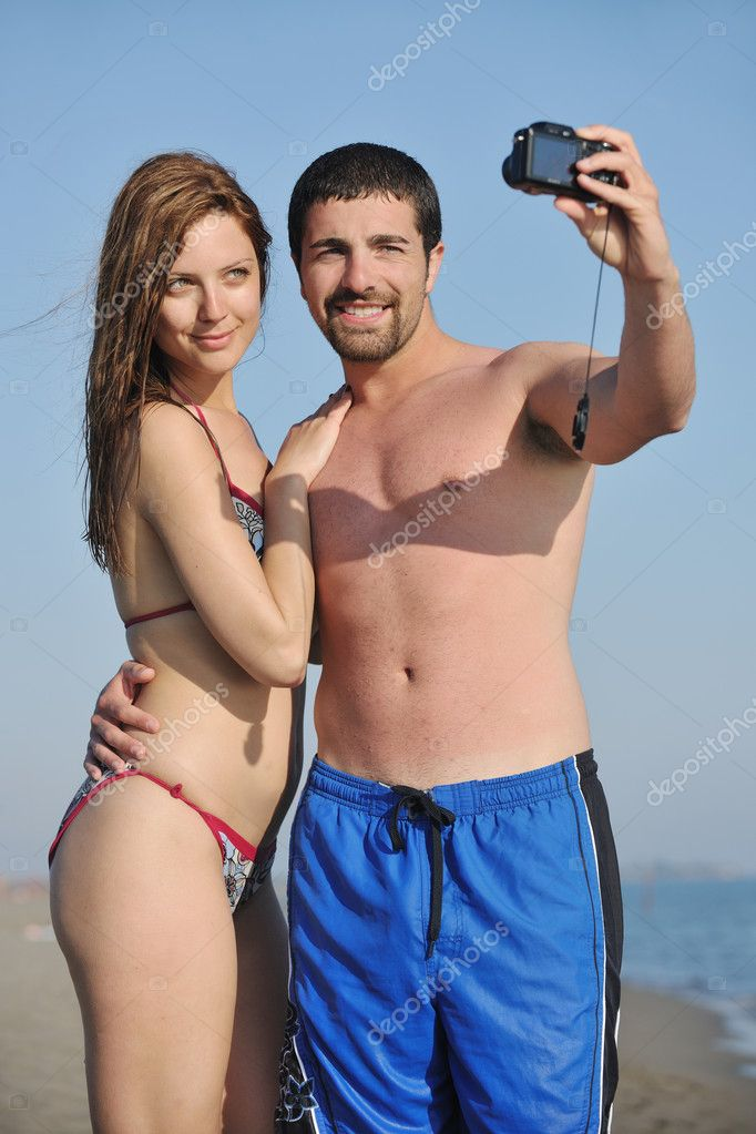 Happy young couple in love taking amateur self portrait photos on beach