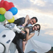 Just married couple on the beach ride white scooter - Stok fotoğraf