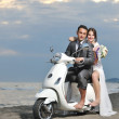 Just married couple on the beach ride white scooter — Stock Photo #5839878