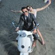 Just married couple on the beach ride white scooter - Lizenzfreies Foto