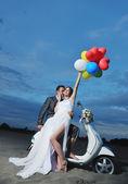 Yeni evli çift beach beyaz binmek scooter üzerinde — Stok fotoğraf