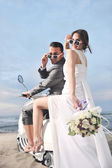 Just married couple on the beach ride white scooter — Zdjęcie stockowe