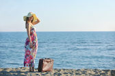 Woman with suitcase on the beach — Stock Photo