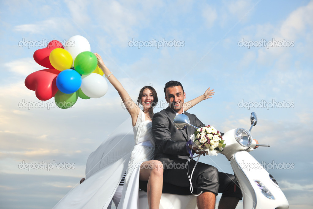 Wedding sce of bride and groom just married couple on the beach ride white scooter and have fun — Stock Photo #5843066